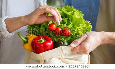 Tomatoes in a reusable bag in the hands of a young woman. Zero waste concept Stock photo © galitskaya