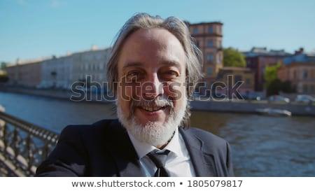 Stock photo: Senior businessman taking a call outdoors