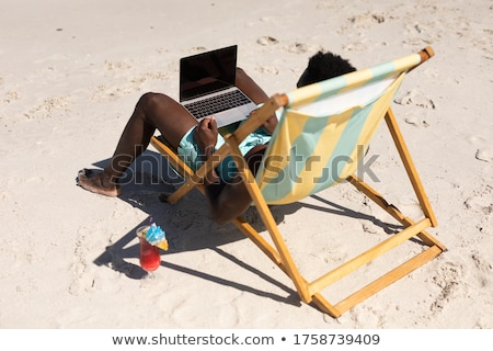 Man on a chair at the beach with his laptop Stock photo © photography33