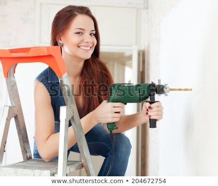Foto stock: Female Labourer Drilling Hole In Wall