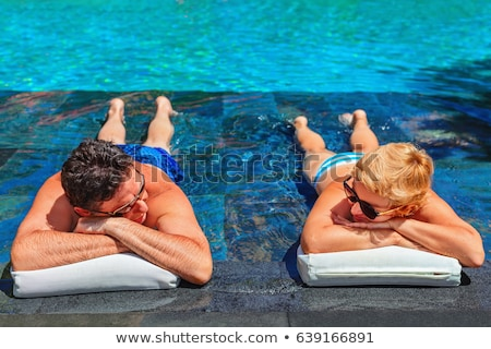 Stock photo: Older man relaxing by a luxurious pool
