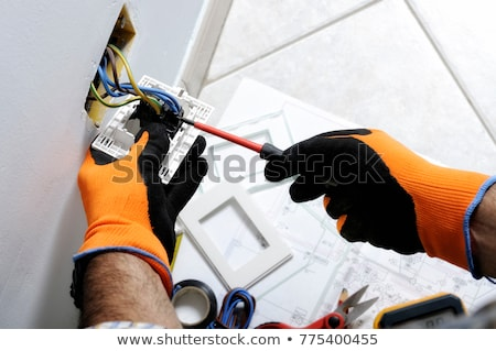 Electrician fixing wall electrics Stock photo © photography33