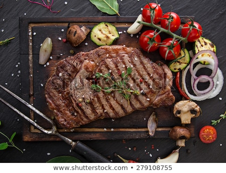 delicious beef steaks on wooden table stock photo © kesu