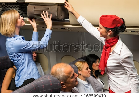 Flight attendant help passenger with luggage cabin Stock photo © CandyboxPhoto
