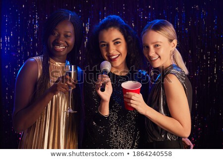 drie · glimlachend · vrouwen · dansen · zingen · karaoke - stockfoto © dolgachov