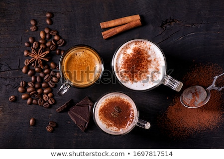 espresso with milk froth cocoa powder and cinnamon sticks stock photo © rob_stark