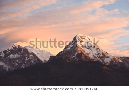 Mountain inspirational beautiful sunset landscape in Himalaya Mountains. Himalayas Annapurna IV(7525m) and Annapurna II(7937m) peaks over blue sky. Looking at mountains landscape view from Pokhara city, Nepal.