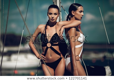 Young beautiful girl in swimsuit posing on the yacht Stock photo © deandrobot