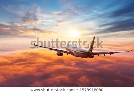 Avion aile battant au-dessus nuages coucher du soleil Photo stock © nalinratphi