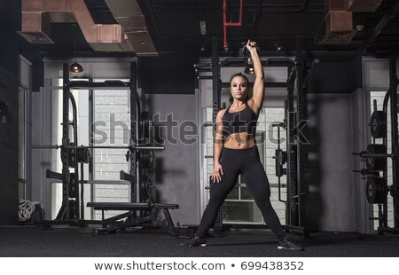 Woman lifting a kettle bell over her head Stock photo © sumners
