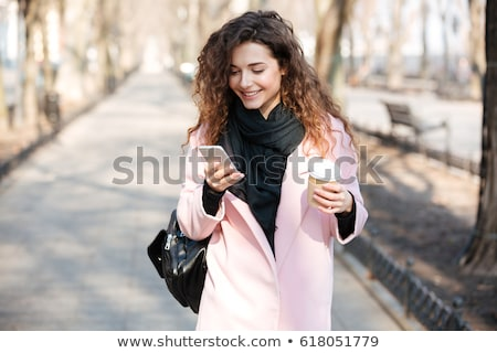 Young woman wearing pink coat walking in the sunny city Stock photo © deandrobot