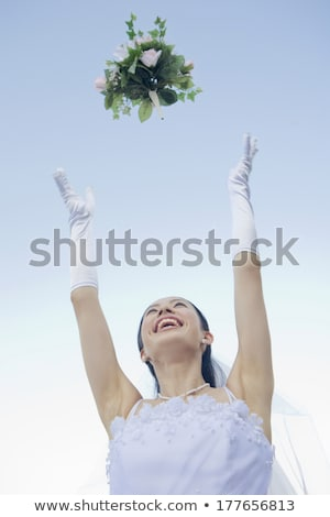 Asian bride tossing a bouquet of flowers. Stock photo © RAStudio