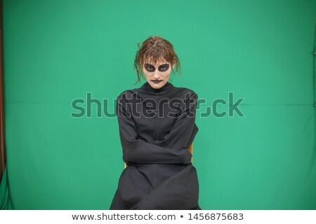 pretty brunette woman with make up like demon at halloween stock photo © iordani