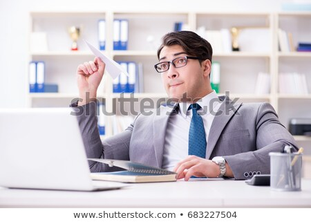 businessman working on a laptop dreams of flying in an airplane stock photo © studiostoks