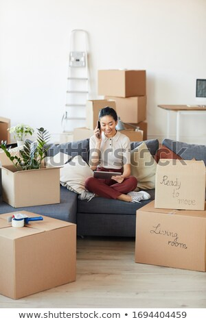 Woman on phone and unpacking boxes Stock photo © IS2