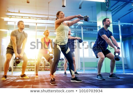 young woman flexing muscles with kettlebell in gym Stock photo © dolgachov