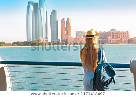 Traveler woman looking at Emirates Palace and skyscrapers of Abu Stock photo © dashapetrenko