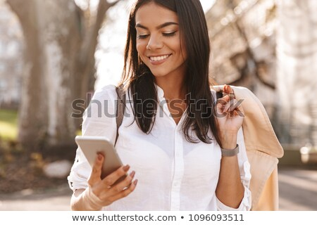 Image of Pleased brunette woman in shirt standing outdoors Stock photo © deandrobot