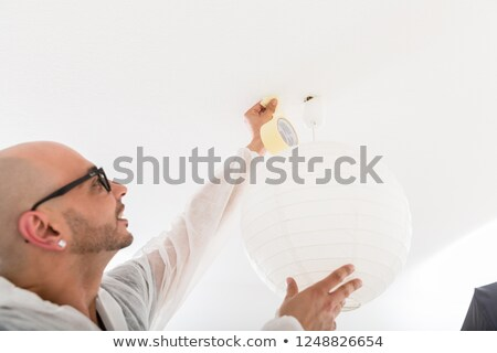 male decorator fixing the tape on ceiling stock photo © kzenon