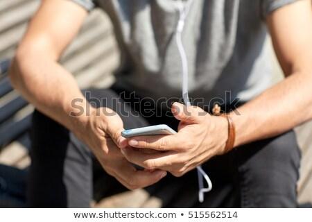 Közelkép férfi okostelefon fülhallgató drót emberek Stock fotó © dolgachov