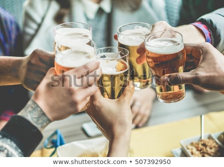 group of young hipsters men and women smiling and drinking beer stock photo © deandrobot