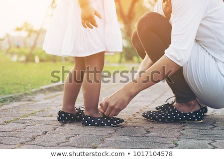Stock photo: Mother is tying a shoe of a child