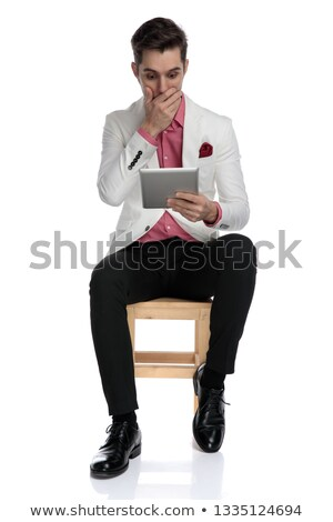 shocked  man covering his mouth while reading news on tablet Stock photo © feedough