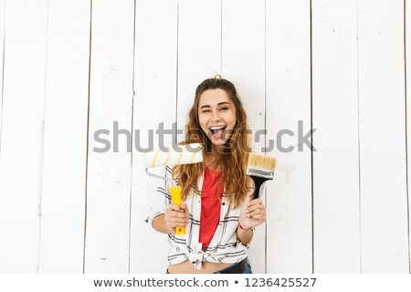 Image of lovely woman 20s holding roller and brush, while painti Stock photo © deandrobot