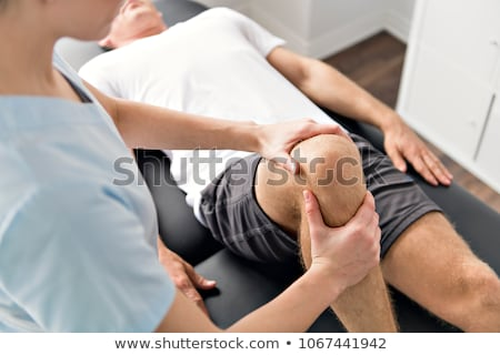 Patient at the physiotherapy doing physical exercises with his therapist Stock photo © Lopolo