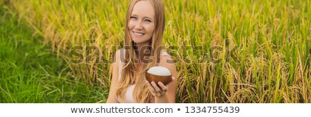 A woman is holding a cup of boiled rice in a wooden cup on the background of a ripe rice field Stock photo © galitskaya