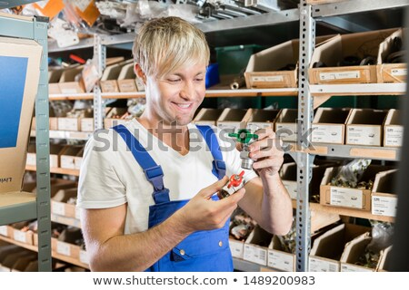 Happy worker comparing two valves in the warehouse of a sanitary shop Stock photo © Kzenon