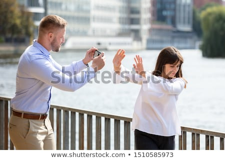 Woman Refusing Man Taking Her Photo On Mobile Phone Stock photo © AndreyPopov