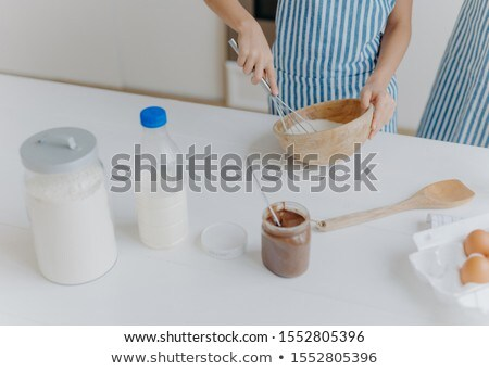 Cropped view of kid in apron whisks ingredients in bowl with beater, busy cooking and helping mother Stock photo © vkstudio