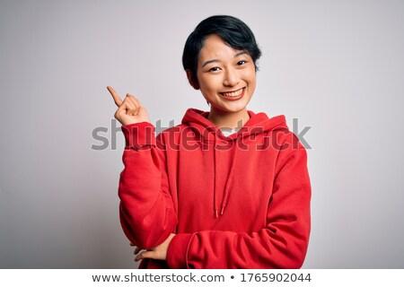 ázsiai fiatal nő mosolyog ujj száj fehér Stock fotó © bmonteny