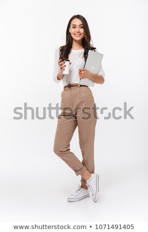 Full-length portrait of a young beautiful woman standing on gray background Stock photo © deandrobot