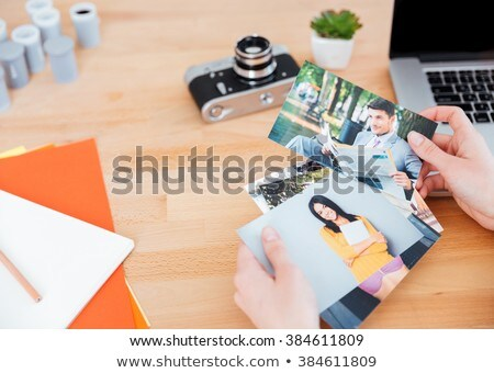 young woman photographer holding photos of model in office stock photo © deandrobot
