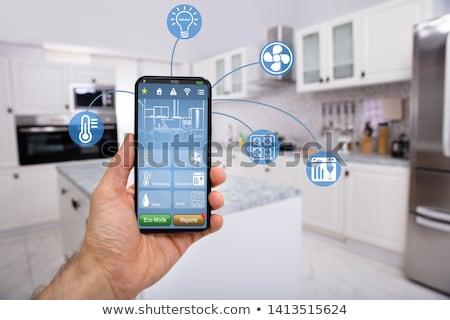 Kéz tart mobil okos otthon irányítás Stock fotó © AndreyPopov