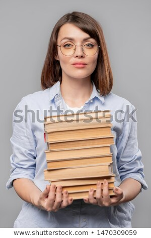 Young serious teacher of literature holding stack of books Stock photo © pressmaster