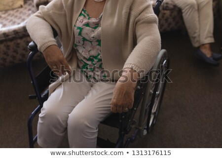 Mid section of disabled senior woman on wheelchair relaxing at home Stock photo © wavebreak_media