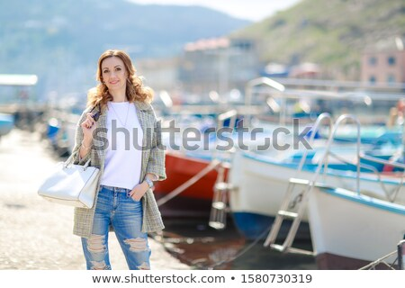 Young beautiful model during vacation walks in the Bay with parked yachts Stock photo © ElenaBatkova