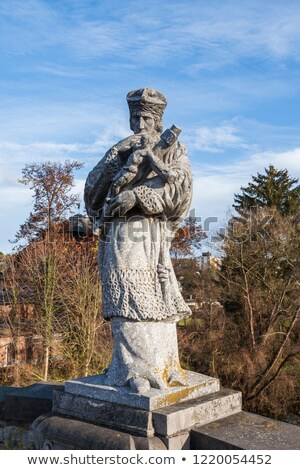 Statue of bishop Nepomuk with a cross at the old river lahn  bri Stock photo © meinzahn