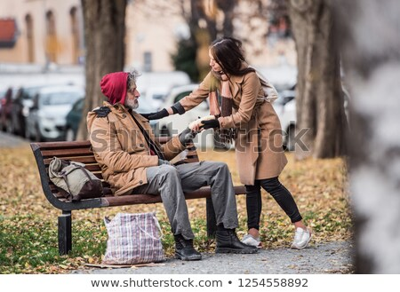 Young woman in grey coat sitting on a bench Stock photo © dariazu