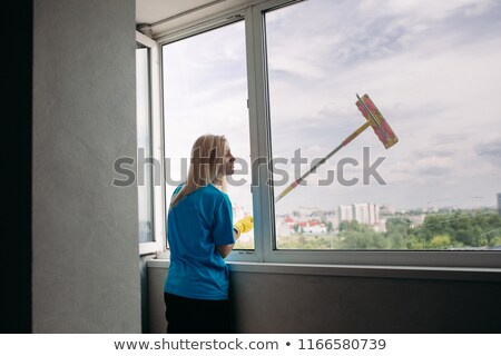 View of young blonde girl cleaning large open window. Stock photo © studiolucky