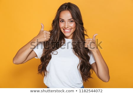 Smiling pretty girls gesturing thumbs-up Stock photo © stockyimages