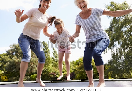 Woman jumping in air in garden Stock photo © IS2