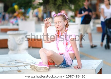 A teenage girl sits on a bench in a public Park and shows a gesture that she is all right Stock photo © ElenaBatkova