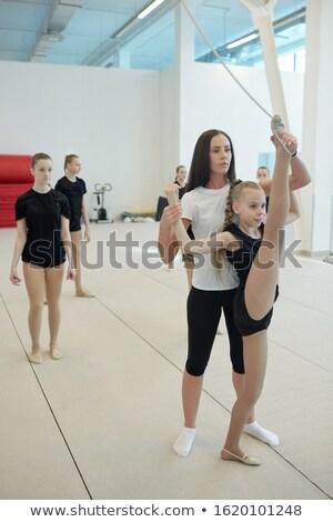 Cheerleading teacher supporting girl doing vertical standing split Stock photo © pressmaster