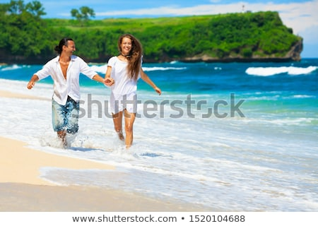 Outdoor portrit of lovely married couple walk together, keep hands together, enjoy nice weather. Smi Stock photo © vkstudio