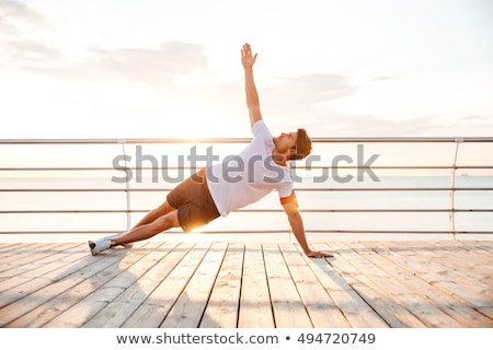 Fitness planking workout man doing plank exercise on beach at sunset. Sexy shirtless male athlete st Stock photo © Maridav