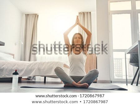 Woman relaxing doing yoga on her bed stock photo © photography33